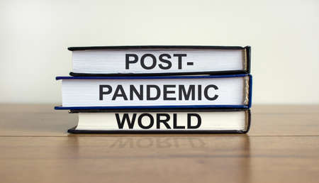 Books with text 'post-pandemic world' on beautiful wooden table, white background. Business and post-pandemic concept. Copy space. Imagens