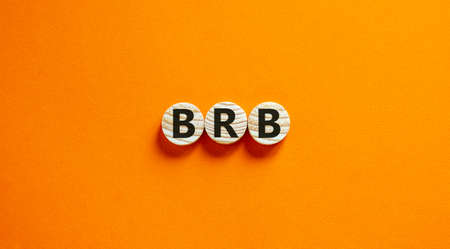 Wide view image of BRB abbreviation spelled on wooden circles. Placed over beautiful orange background, copy space. Business concept.