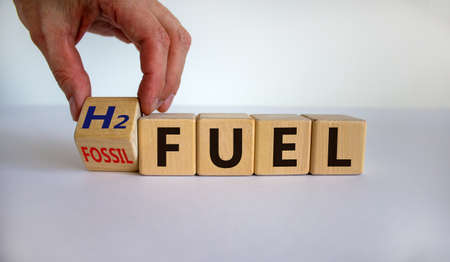 Hand turns a cube and changes the expression 'fossil fuel' to 'H2 fuel'. Beautiful white background, copy space. Concept.