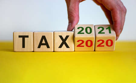 Business concept of planning 2021. Male hand flips wooden cube and change the inscription 'tax 2020' to 'tax 2021'. Beautiful yellow table, white background, copy space. Standard-Bild