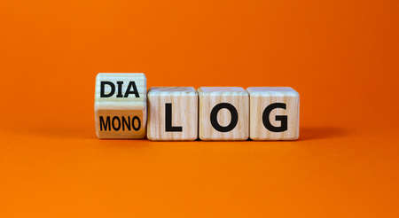 Fliped a cube and changed the German word 'monolog' - 'monologue' in English to 'dialog' - 'dialogue' in English. Beautiful orange background. Business concept. Copy space.