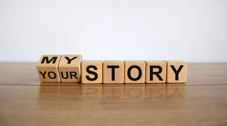Turned cubes and changed the expression 'my story' to 'your story'. Beautiful wooden table, white background, copy space. Business concept.