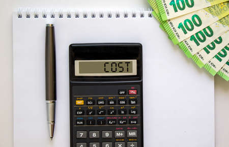 Calculator with word 'cost', white note, euro bills, pen. Business concept. Beautiful white background, copy space.