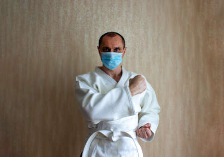 COVID-19 Pandemic Coronavirus concept. A young strong man in a white kimono for sambo, jiu jitsu and other martial arts with a blue medical gloves and medical mask.