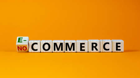 Turned the cube and changed the expression 'no commerce' to 'e-commerce'. Beautiful orange background. Business concept. Copy space.