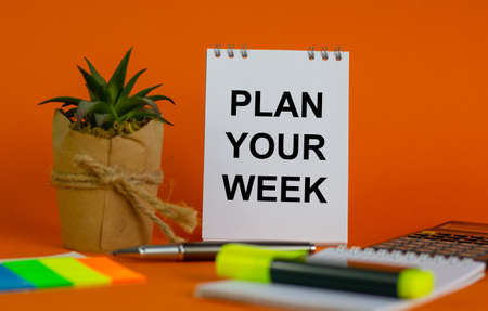 White note with inscription 'plan your week' on beautiful orange background, colored paper, metalic pen, yellow marker, flowerpot with a plant and calculator. Business concept. Zdjęcie Seryjne