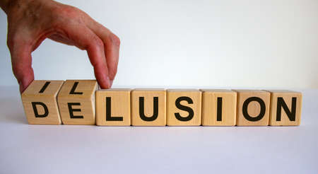 Hand turns a cube and changes the word delusion to illusion. Beautiful white background. Business concept. Copy space.