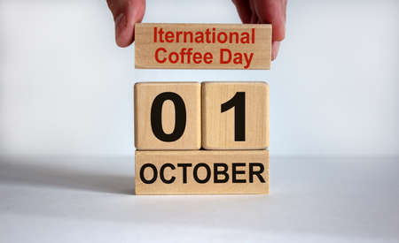 Male hand puts a block with the inscription 'international coffee day' on cubes with the date october 01. Beautiful white background, copy space.
