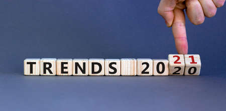 Business concept of planning 2021. Male hand flips wooden cubes and changes the inscription 'TRENDS 2020' to 'TRENDS 2021'. Beautiful gray background, copy space.
