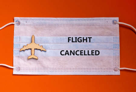 Coronavirus flight cancellations concept. Face mask and airplane toy on orange background. Words 'flight canceled'.