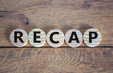 The word 'recap' on wooden circles on beautiful wooden table. Beautiful background, copy space. Business concept.