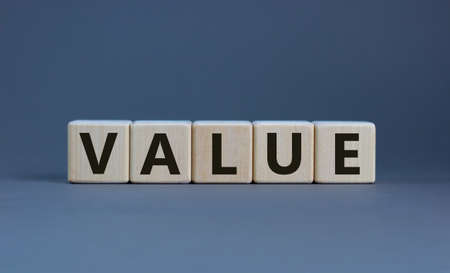 The word 'value' on wooden cubes on a beautiful gray background, copy space. Business concept. Stockfoto
