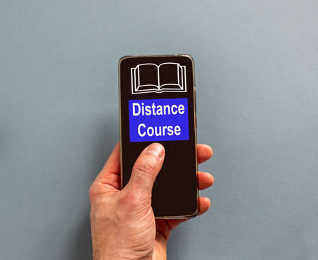 Male finger clicks on smartphone screen with a words 'distance course' on the blue background. Book sign. Concept of online education. Reklamní fotografie
