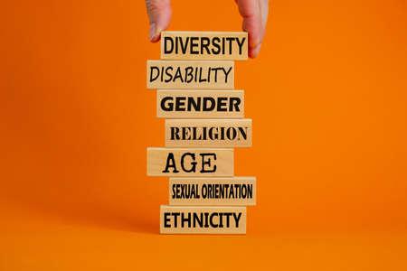 Diversity ethnicity gender age orientation religion disability words written on wooden block. Male hand. Beautiful orange background. Equality and diversity concept. Standard-Bild