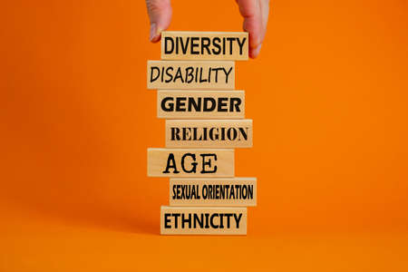 Diversity ethnicity gender age sexual orientation religion disability words written on wooden block. Male hand. Beautiful orange background. Equality and diversity concept.
