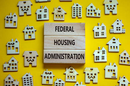 Wooden blocks form the words 'federal housing administration', miniature wooden houses. Beautiful yellow background, copy space. Business concept.