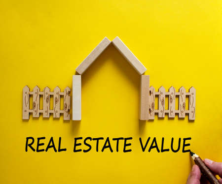 Hand writing 'real estate value' on beautiful yellow background. Model of a wooden house. Male hand, wooden fence. Copy space. Business concept.