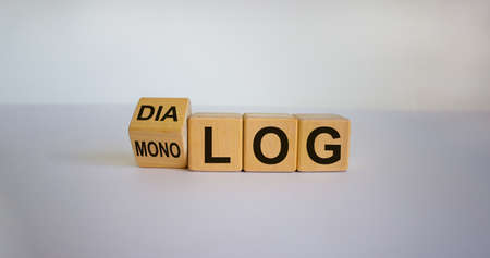 Fliped a cube and changed the German word 'monolog' - 'monologue' in English to 'dialog' - 'dialogue' in English. Beautiful white background. Business concept. Copy space.