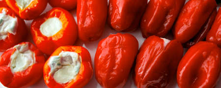 Red bell peppers stuffed with meat, rice and vegetables on cast white plate. Food concept.