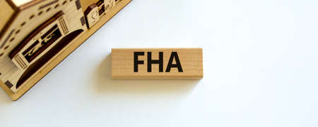 Wooden block with word 'FHA, federal housing administration' near miniature house. Beautiful white background