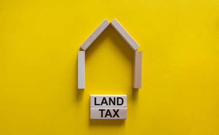 Model of a wooden house. Words 'land tax' on wooden blocks. Copy space. Business concept. Beautiful yelllow background. Banco de Imagens