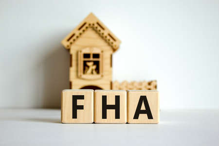 Wooden cubes form the word 'FHA, federal housing administration' near miniature house. Beautiful white background
