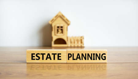 Blocks form the words estate planning in front of a miniature house. Beautiful wooden table, white background.