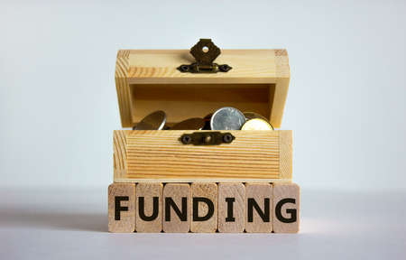 Concept word 'funding' on wooden blocks on a beautiful white background, small chest with coins. Business concept, copy space.