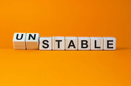 Turned cubes and changed the word 'unstable' to 'stable' or vice versa. Beautiful orange background. Business concept. Copy space.