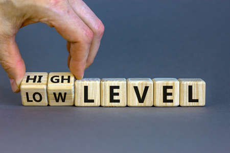 Hand turns a cubes and changes the expression 'low level' to 'high level' or vice versa. Beautiful gray background. Business concept, copy space.
