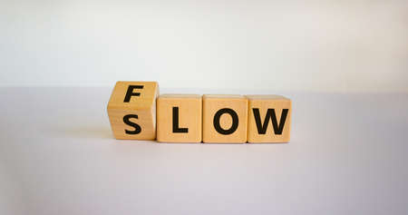 Be slow or in the flow. Turned a cube and changed the word 'slow' to 'flow'. Beautiful white background, copy space. Business concept. Banque d'images
