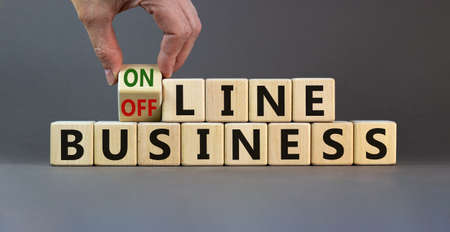 Time to online business. Male hand turns the cube and changes the expression 'offline business' to 'online business'. Beautiful gray background. Business concept. Copy space.