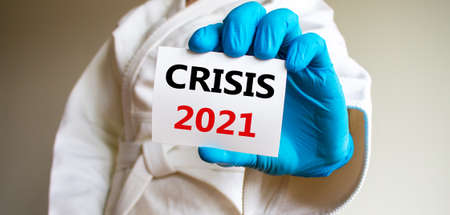 COVID-19 Pandemic Coronavirus concept. A young strong man in a white kimono for sambo, jiu jitsu and other martial arts with a blue medical gloves. White card with words crisis 2021.