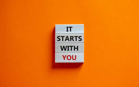 Wooden blocks form the words 'it starts with you' on beautiful orange background. Business concept. Copy space.