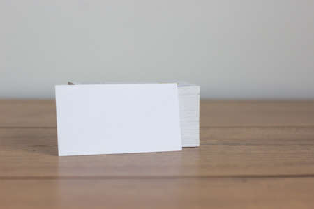 Perspective view of white business card on beautiful wooden table. White background, copy space. Stock Photo