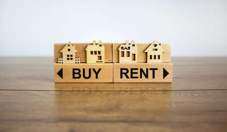 Wooden blocks form the words 'buy, rent' and oppositr arrows, miniature house, wooden table. Beautiful white background, copy space. Business concept.
