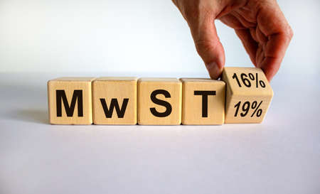 German stimulus packages after the corona crisis. Hand turns a cube and changes the expression 'MwST 19' to 'MwST 16'. Beautiful white background. Copy space.