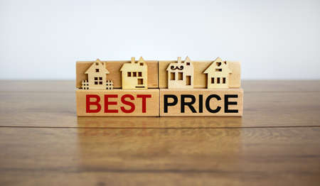 Models of a wooden house. Words 'best price' on wooden blocks. Copy space. Business concept. Beautiful wooden table, white background.