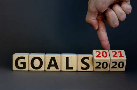 Hand turns cubes and changes the expression 'goals 2020' to 'goals 2021'. Beautiful gray background. Business concept. Copy space.