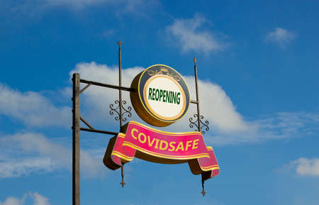Street signs with text 'reopening, covidsafe' on metal pole. Blue sky background. Charity. Covid-19 pandemic concept, copy space.