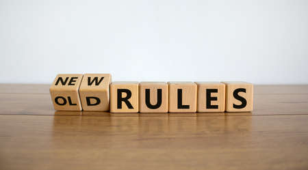 Turned cubes and changed words 'old rules' to 'new rules' on a beautiful wooden table, white background. Business and covid-19 pandemic concept. Foto de archivo