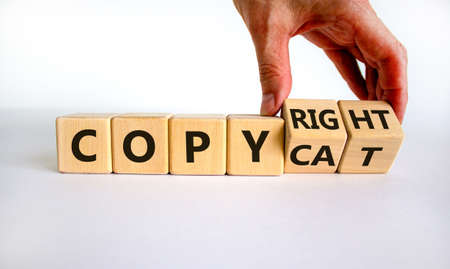 Hand flips cubes and changes the word 'copycat' to 'copyright'. Beautiful white background. Business concept. Copy space.