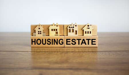 Wooden blocks form the words 'housing estate', miniature house, wooden table. Beautiful white background, copy space. Business concept.