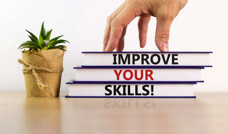 Books with text 'improve your skills' on beautiful white table. Male hand, house plant. White background. Business concept. Copy space.