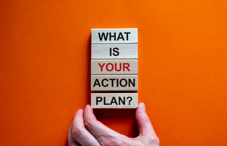 Male hand placing a block with word 'plan' on a blocks tower with words 'what is your action plan'. Beautiful orange background. Business concept. Copy space. 写真素材