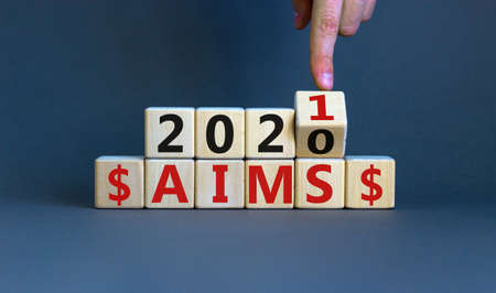Business concept of planning 2021. Male hand flips wooden cube and change the inscription 'Aims 2020' to 'Aims 2021'. Beautiful gray background, copy space.