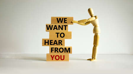 Wooden blocks with text 'we want to hear from you'. Wooden model of human. Beautiful white background, copy space. Business concept.