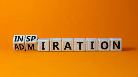 Turned cubes and changed the word 'inspiration' to 'admiration' on wooden cubes. Beautiful orange background, copy space. Business concept.
