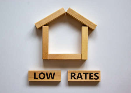 Wooden blocks form the words 'low rates' near miniature house. Beautiful white background, copy space. Business concept.