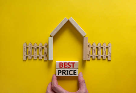 Model of a wooden house. Words 'best price' on wooden blocks. Male hand, wooden fence. Copy space. Business concept. Beautiful yelllow background.